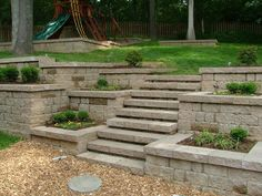 This stone walkway leads up to a stairway that matches the scene perfectly. The neutral gray stones in this setup makes the colors around it seem much more vivid and bright. Using the retainer walls on either side as planter's boxes makes the scene uniformed without taking too much away from the natural ambience. Plants with vivid flowers would look great filling these stone garden boxes.