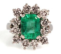 This stunning 3 carat Emerald is set in a halo of 2.50 carats of round brilliant diamonds prong set in platinum. The ring measures 19.3mm at the top, rises 8.8mm above the finger, tapering to 3.2mm wi
