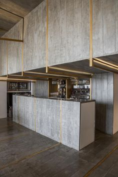 Sleek and modern bar with brass details and concrete.