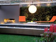 A contemporary outdoor fireplace is the focal point in a urban styled outdoor garden pavilion.