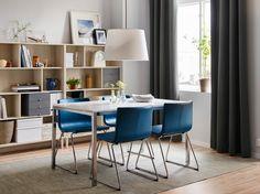 Eettafel met tafelblad in wit glas en verchroomde poten in combinatie met vier blauwe, leren stoelen met verchroomde poten