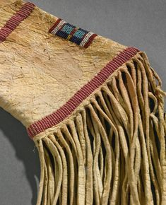 Crow Beaded Hide Rifle Scabbard of classic tapering form, composed of finely tanned hide, sinew sewn with glass beadwork in outline white and other numerous colors against a green ground, with pairs of triangles on each side of the barrel, the butt with parallel bands enclosing a panel with a bar motif, trimmed with thick, supple fringe and a pair of triangular suspensions decorated with red stroud and white beads. length 40 in.  ДА3. Sotheby's ARTS OF THE AMERICAN WEST 21 MAY 2014 NEW YORK