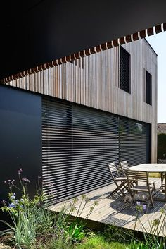 Adjustable shutters function as a brise soleil to regulate the amount of sunlight reaching the interior during the warmer months.. Villa B by Tectoniques