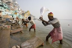 Pounding laundry on banks of the Ganges River.