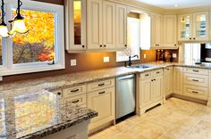 Bright, welcoming tones throughout this kitchen: beige tile flooring with near-matching cabinetry, mocha brown backsplash paint and speckled marble countertops all around.