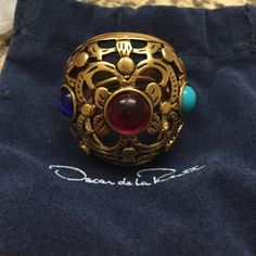 Gold Oscar de la Renta cocktail ring Never been worn. Still in original box with original tags. Very classy yet unique statement ring, perfect for parties. Gold with red, indigo, and cyan stones. Oscar de la Renta Jewelry Rings