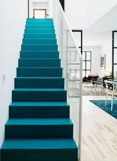 Fantastic sleek modern blue stairs. A touch of playfulness added to the decor in this apartment.
