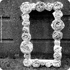 Tutorial: Make newspaper roses -- used in this case to decorate a frame.