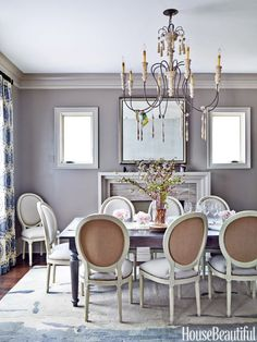 "The dining room is infused with silvery tones ""for elegance,"" says Kong, who chose Sherwin-Williams's Backdrop for the walls and refinished the owners' cherry dining table in a watery gray. Zentique's Medallion chairs backed in burlap echo the living room's gold accents. Hannah chandelier, Currey & Company. Curtains, Robert Allen's Medallion Band."