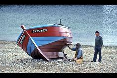 On faisait la pause-café sur la terrasse du Café du Port à Omonville. Sur la plage de galets, Un pêcheur donnait un coup de peinture à son bateau, quand un copain passa faire la causette. Ça valait bien une photo.