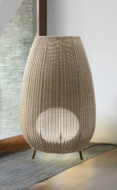A lamp shade composed of hand wrapped polyethylene synthetic fiber makes this indoor-outdoor floor lamp a statement piece.