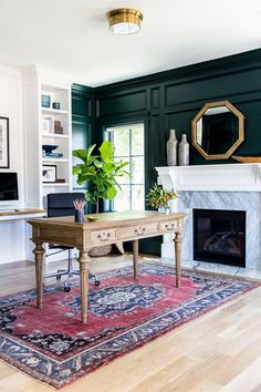 Green-black paneled walls and marble fireplace || Studio McGee