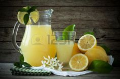 Jug and glass with lemon juice decorated with fresh lemons and mint leaves. Stock Photo