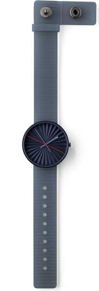 Plicate designed by Benjamin Hubert for the Nava brand is modeled after the pleats found in folded paper fans. The strap utilizes the same pleats and has been designed to let the air flow between the band and arm, preventing the build up of dirt. The standard buckle has been replaced by an asymmetrical clasp, which allows users to easily remove the watch, while keeping it securely fastened.