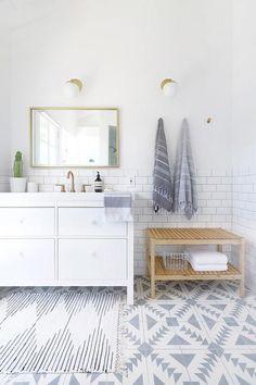 Beautifully designed gray and white bathroom features an Urban Outfitters Plum & Bow Connected Stripe Rag Rug placed on Cement Tile Shop Tulum II Tiles in front of an Ikea Hemnes/Odensvik Washstand adorning CB2 Marble White Disc Drawer Pulls and a brass faucet by Delta.