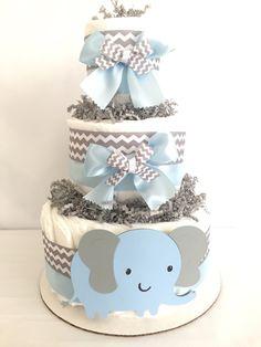 ein blauer elefant mit großen grauen ohren und schwarzen augen, eine windeltorte junge selber machen, eine dreistöckige torte aus vielen weißen windeln und mit großen blauen und gelben schleifen