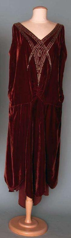 WINE VELVET EVENING GOWN, c. 1928  V-neck front, drop waist w/ asymmetrical skirt, rhinestone & bead embellishment on sleeveless bodice