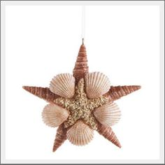 **SOLD OUT** Sea star shell ornament. Spiral and scallop shells are arranged to create the shape of a sea star. A dusting of glittering sand completes this chic, seashell ornament to adorn your tree.