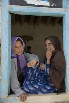 Girls sit in the window laughing as they wait for classes to begin at Bam Sarai School in Afghanistan.