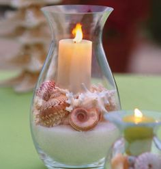 A hurricane candle holder with shells.