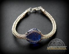 Dragon Eye Bracelet.  This bracelet has been thoroughtly handmade with an ancient technique known as viking knit wich appears in luxurious jewelry of ancient times.This time, the piece is made in silver plated wire of 0.3mm thick. A deep blue glass sphere completes the item. One size (16.5 cm / 6.5 inches). Made in Spain.