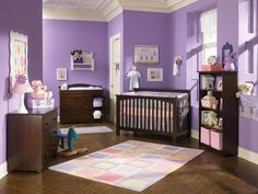 Here we have a full spectrum of pink and purple shades, between darker wall paint and lighter bedding shades, with multicolored central patterned rug over natural wood floor. Dark hardwood dressers and crib anchor the theme in natural tones.