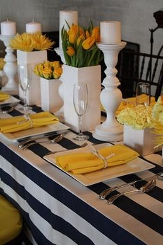 table setting ... modern look ... black and white striped table cloth ... white accessories with pops of yellow from flowers and napkins
