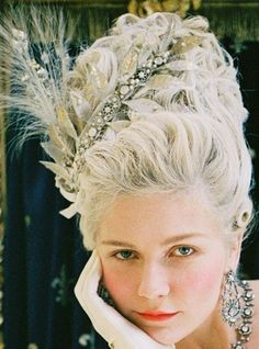 Marie Antoinette - Wear your hair in tight curls with tons of volume and dress it up with flowers, feathers, bows, household objects, dessert, whatever. Don't forget to pile on the jewels, gloves, ruffles, lace and blush and be glad this isn't still a day-to-day routine.