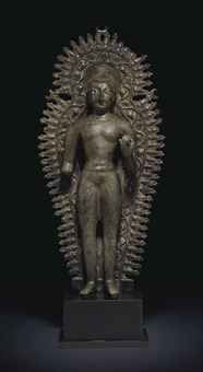 A highly important and rare silver-inlaid bronze figure of the youthful Buddha, Gandhara or Kashmir, circa 7th century
