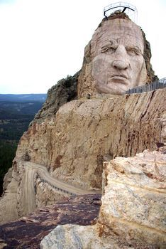 CRAZY HORSE MEMORIAL in progress. The 563-foot-high mountain carving-in-the-round will dominate the horizon. A poem by Korczak will be carved on the mountain in letters three feet tall. The 350-foot diameter, hogan-style Indian Museum of North America will be across the reflecting pool from the mountain.The American Indian University & Medical Training Center will rise on either side of the Avenue of the Chiefs. The avenue will be lined with sculptural portraits of famous Native Americans.
