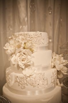 White wedding cake with white flowers and white lace.