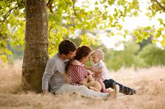 adorable family of three, against a tree, stand back, have a moment