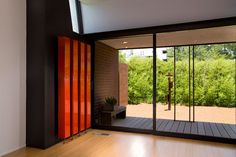 Architecture Design, New Homes Orange Wall Lighting Dark Floor Sliding Glass Doors: OKasian House with New Homes by Fitzsimmons Architects