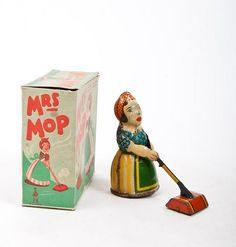 Mrs. Mop | She Sweeps the floor forwards, backwards, in all directions. Made in England, ca. 1950 11.5 x 12 cm. In original box. - added 2 tin seals keeping a ball in the air, both with winding mechanism. *Rare tin toy. Perhaps even small children were not entirely convinced by this seemingly innocent stereotypical cleaning lady. Seals, clowns or cars were more marketable.