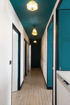 Un couloir peint en bleu et blanc, avec des encadrements de porte constrastés en noir.