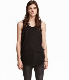 White. Tank top in slub jersey with raw edges at neckline and armholes. Rounded hem.