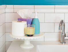 IF I had a bathtub - TOILETRY STAND  De-clutter bathroom counters by gathering essentials like soap, candles and toilet paper on a cake stand. If you take off your rings before hand washing, add a small dish to hold them. Get more tips for keeping countertops clean>>