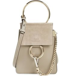 Iconic equestrian-inspired hardware gleams against the chic mix of buttery-soft calfskin suede and leather on Chloé's Faye compact bag.