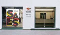 Optica Eyewear Store with Logo Design on Wall by Vlad Likh