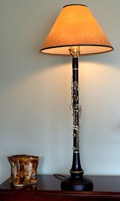 This lamp was made from a clarinet that has seen better days, as it doesnt appear playable. It is a D.Noblet Clarinet that is made of wood, and