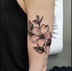 Hibiscus flower tattoo on the left upper arm.
