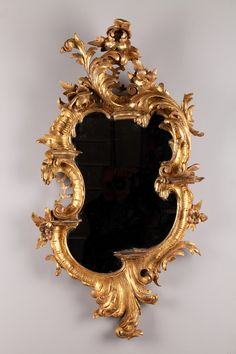 18th century Venetian-style mirror. It is made of giltwood and is richly decorated with scrolls, flowers and foliage in Rococo style. The mirror is provided with four small consoles with curved lines. Italian work.