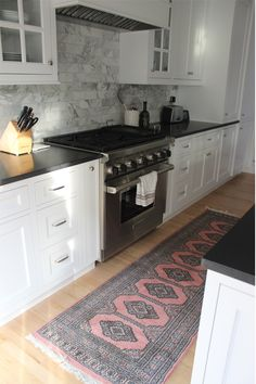Rug in the kitchen.  Nice marble backsplash with black counters (which is seemless with the black top of the stove) and white cabinets.
