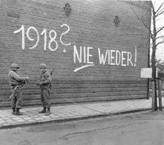 "Somewhere in Germany, Feb 1945: US Army technicians work on telephone wiring. The graffiti behind them reads: ""1918? Never Again!"" referring of course to the German defeat in WW1."