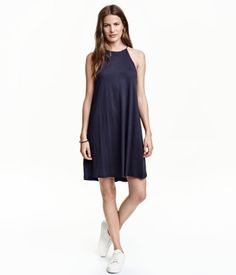 Dunkelblau. Kurzes Jerseykleid mit schmalen Trägern. Modell mit schmalem Oberteil, ausgestelltem Rock und geknöpftem Nackenschlitz. Oben gefüttert.