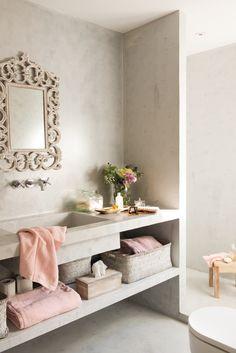 un baño de microcemento y toallas en rosa