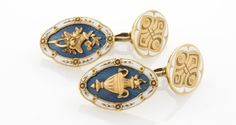 Antique Gold, Blue and White Enamel Cufflinks  A pair of Antique 18 karat gold, blue and white enamel cufflinks. One of the oval links features an amphora and the other a flowered hat with blue guilloche enamel background. The opposite oval link is an engraved pattern with white enamel.  Circa: 1900