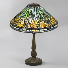 """This is not contemporary - image from a gallery of vintage and/or antique objects. """"Daffodil"""" Tiffany Lamp  A Tiffany Studios New York glass and bronze """"Daffodil"""" table lamp, featuring a leaded glass shade depicting daffodil flowers against a blue ground, atop a patinated bronze """"Mock Turtle"""" base."""