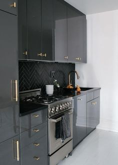 Amazing kitchen features gray lacquered cabinets adorned with gold pulls paired with black countertops and a black herringbone tiled backsplash.