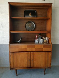 Mid Century china cabinet displays vintage barware and Courac platters.  Available on Phoenix Craigslist.